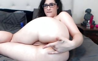 Nerdy wench in glasses demonstrates her incredible ass and fingers it
