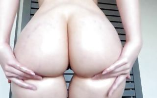 Young seductive brunette with a big ass fingers her clit and poses